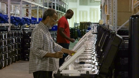 FILE - This Sept. 22, 2016 file photo shows employees of the Fulton County Election Preparation Center in Atlanta test electronic voting machines. A security researcher disclosed a gaping security hole at the outfit that manages Georgia's elections. The lapse, which left the state's 6.7 million voter records and other sensitive files exposed to hackers, was first reported Wednesday, June 14, 2017, by the news site Politico. (AP Photo/Alex Sanz)