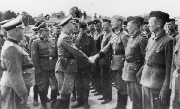 This 1942 photo shows Heinrich Himmler, center left, shaking hands with new guard recruits at the Trawniki concentration camp in Nazi occupied Poland. (Public prosecutor's office in Hamburg via the United States Holocaust Memorial Museum and AP)