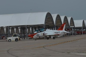 A T-45 Goshawk aircraft is towed from the hangar to the aircraft protective enclosures on the Naval Air Station Kingsville, Texas, flight line. (NAS Kingsville via Facebook)