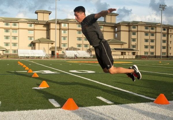 Petty Officer 3rd Class Lawrence, an aviation electronics technician with Marine Aviation Logistics Squadron 24 soars throught the air as he conducts a standing long jump for distance May 18, 2015, at Pop Warner Field. Lawrence attempted the jump three times and used the longest jump of the three as his assessment score.