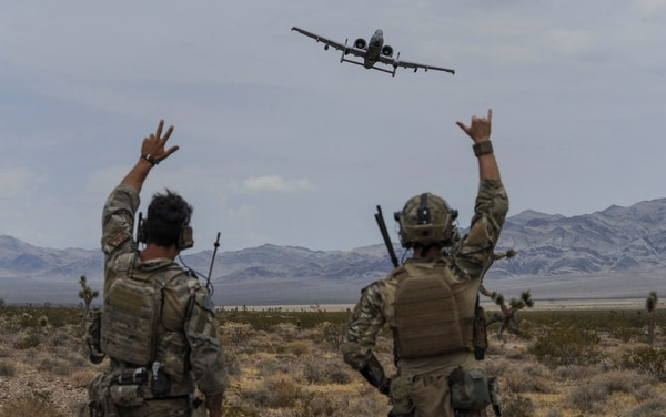 Joint terminal attack controllers wave at an A-10 Thunderbolt II attack aircraft during an exercise on the Nevada Test and Training Range in July 2017. (Senior Airman Kevin Tanenbaum/Air Force)