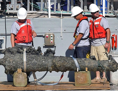 In this Oct. 26, 2011 photo, researchers led by the N.C. Department of Cultural Resources' Underwater Archaeology Branch rest a recovered 2,000-pound cannon on the back of a NOAA research vessel from the wreck of the pirate Blackbeard's ship, which has been on the ocean floor off the North Carolina coast for nearly 300 years in Beaufort, N.C. (Chuck Beckley/The Jacksonville Daily News via AP)