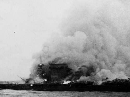 The aircraft carrier burns and sinks after being abandoned by the crew on May 8, 1942 during the Battle of Coral Sea. Note planes parked aft, untouched by the fire. (U.S. Naval History and Heritage Command)