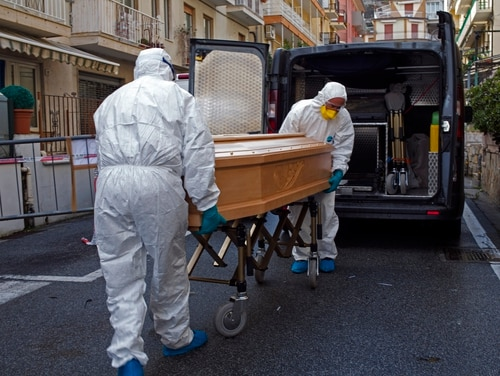 Medical staff wearing protective suits carry the coffin containing the body of Assunta Pastore, 87, after she passed away in her room at the Garden hotel in Laigueglia, northwest Italy, Liguria region, on March 1. The woman, part of a group of elderly tourist from the Lombardia region, tested positive of the COVID-19. (AP)