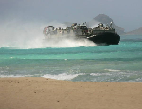 A U.S. Navy Landing Craft Air Cushion (LCAC) amphibious vehicle rushes the beach at Bellows Air Force Station on Oahu, Hawaii during joint amphibious exercises, as the U.S. Marine Corps and Navy host defense leaders from around the Pacific, Tuesday, May 19, 2015. The first-of-its kind meeting comes as territorial disputes over islands are growing more heated in the region. (AP Photo/Caleb Jones)
