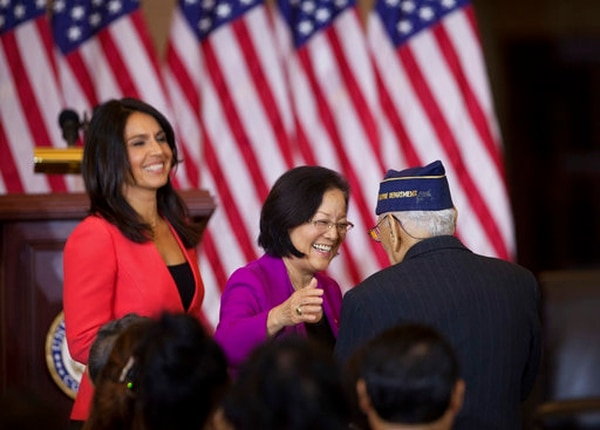 Celestino Almeda, a Filipino World War II veteran, is congratulated by Sen. Mazie Hirono, D-Hawaii, and Rep. Tulsi Gabbard, D-Hawaii, during a ceremony at the Emancipation Hall on Capitol Hill in Washington, Wednesday, Oct. 25, 2017, awarding the Congressional Gold Medal to Filipino veterans of World War II. (Manuel Balce Ceneta/AP)