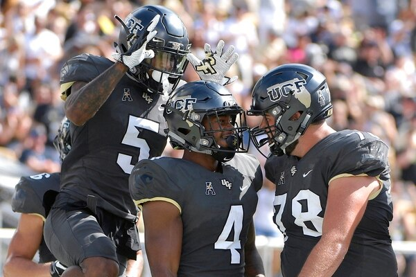Central Florida running back Taj McGowan is congratulated by wide receiver Dredrick Snelson and offensive lineman Wyatt Miller after rushing for a 2-yard touchdown against Navy on Saturday in Orlando. (Phelan M. Ebenhack/AP)