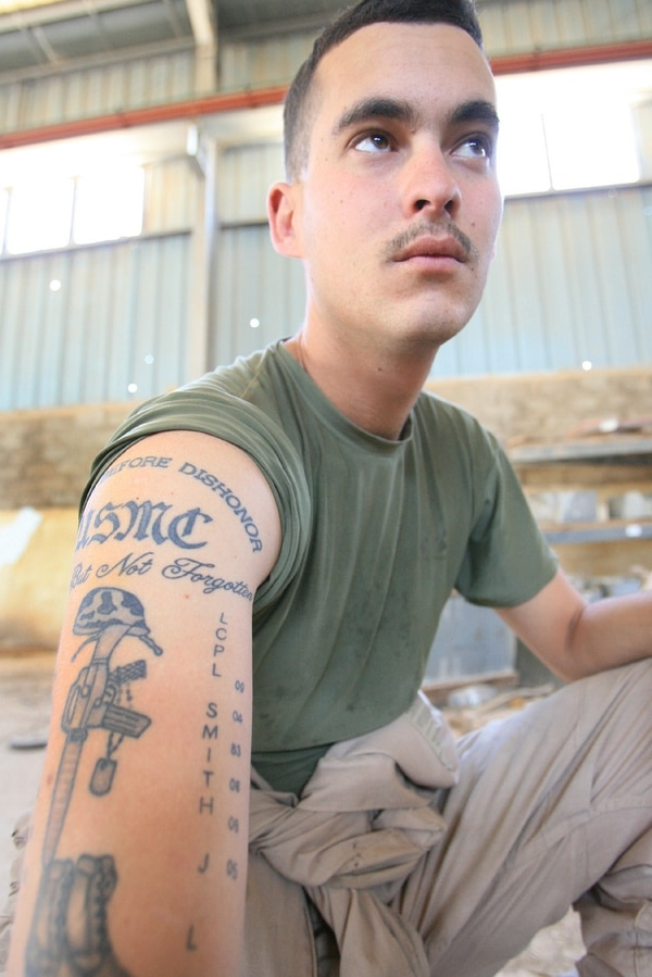 Cpl. Nick I. Jason, 22, from Sarasota, Fla. and an assistant section leader with D Company, 2nd Assault Amphibian Battalion displays the tattoo he got in memory of his friends and fellow Marines, Lance Cpl.'s Jonathan L. Smith and Chase J. Comley, at Camp Smitty, Iraq May 26, 2006. Smith was killed in action June 6, 2005. Jason served with B Company, 2nd Assault Amphibian Battalion last year in Iraq and helped to open the camp that was later named in honor of Smith.