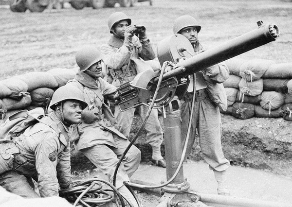 Some of the African American troops manning an anti-aircraft gun on an airfield under construction, somewhere in England, April 12, 1943. Left to right are: T5 Jesse James Draugham, from Bremond, Texas; Private Howard Kibble, from Chicago; acting Sergeant Howell Atkinson, from Fort Worth, Texas, and Private 1st Class, John Brown, from Steucanville, Ohio. (AP Photo)