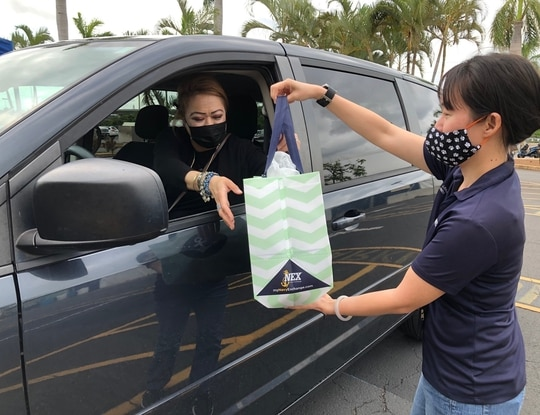 A Navy Exchange associate delivers merchandise to a customer at the designated curbside pickup parking lot at the Pearl Harbor Navy Exchange. (Courtesy photo by Stephanie Lau-Abdul, NEX Pearl Harbor)