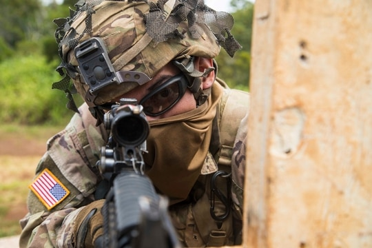 """Spc. Raphael Ramos, a wheeled vehicle mechanic with G Company, 1st Battalion, 27th Infantry Regiment """"Wolfhounds"""", 2nd Infantry Brigade Combat Team, 25th Infantry Division scans his lane during a rifle qualification range May 1, 2020, at Schofield Barracks, Hawaii. Soldiers ensured they kept with social distancing guidelines as they demonstrated proficiency on their assigned weapons and trained on their lethal soldier skills. (Sgt. Thomas Calvert/Army)"""