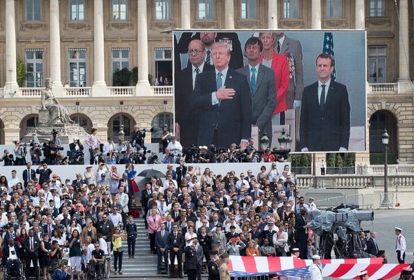 U.S. President Donald Trump and French President Emmanuel Macron are seen on a large screen as they stand during the American National Anthem during Bastille Day parade in Paris on July 14, 2017. (Carolyn Kaster/AP)