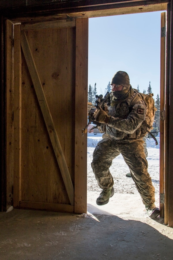 Spc. Fabian Nietert, of 1st Battalion, 297th Infantry Regiment, breaches a simulated hostile building during Arctic Eagle 2018 at the Donnelly Training Area outside of Fort Greely, Alaska, March 1. (Spc. Michael Risinger/Army)
