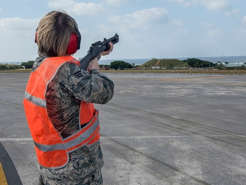 Air Force Senior Airman Monika Neal, an airfield management operations coordinator with the 18th Operations Support Squadron, shoots a pyrotechnic round at a flock of birds to scare them off a runway at Kadena Air Base, Japan, in November 2016. Birds and other wildlife can be sucked into the engines of aircraft and cause severe damage. (Airman 1st Class Corey Pettis/Air Force)