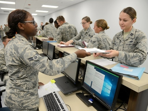 Airman 1st Class Maiesha Buford gives Capt. Theresa Hall her health records during a deployment preparation exercise on Oct. 4, 2017, at Tinker Air Force Base in Oklahoma. The Department of Veterans Affairs last year finalized a 10-year, $16-billion plan to share medical records systems with the Department of Defense. (Kelly White/Air Force)