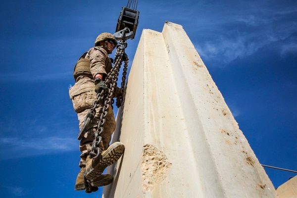U.S. Marine Sgt. Edward Hooper, an electrician with Engineer Company, Combat Logistics Battalion 1, currently deployed in support of Special Purpose Marine Air Ground Task Force-Crisis Response-Central Command 16.1, attaches chains from the hook block of a MAC-50 Crane onto an Alaskan wall at Al Taqaddum Air Base, Iraq, Oct. 25, 2015. The 12-ton T-walls are placed around key structures to provide protection from shrapnel. (U.S. Marine Corps photo by Sgt. Rick Hurtado/Released)