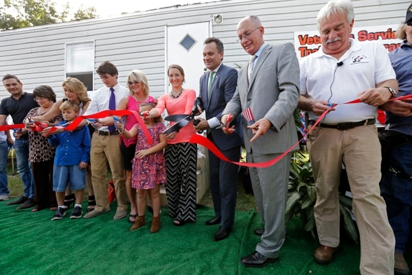 Jefferson Parish President John Young, third right, participates in a ribbon-cutting ceremony for Companions for Life Training Academy, a Veterans Service Dog Training Program & Facility, at the Jefferson Parish Animal Shelter in Harahan, La., Friday, Sept. 25, 2015. Veterans will learn to train service dogs and to teach other military veterans suffering from PTSD, brain injury or other medical problems how to train their own pets to meet their medical or psychological needs. They will be among the first participants in the program to teach veterans, including those who've never worked with canines, to train their own service dogs: animals coming from shelters. (AP Photo/Gerald Herbert)