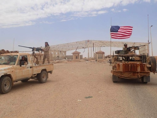 A U.S.-backed anti-government Syrian fighter mans a heavy automatic machine gun, left, next to an American soldier as they take their positions at Tanf, a border crossing between Syria and Iraq.