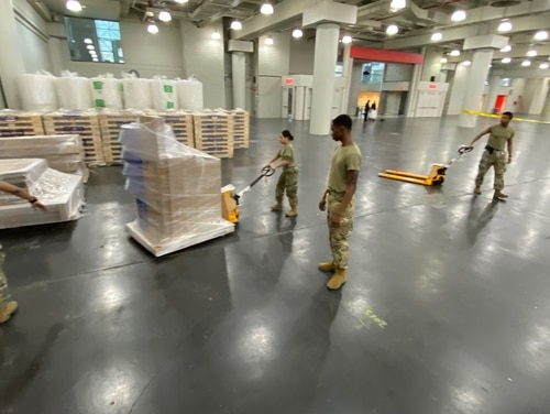 New York Army National Guard Soldiers of the 133rd Composite Supply Company warehouse and inventory the initial shipments of a FEMA Field Hospital for setup at the Jacob Javits Convention Center in New York City March 25, 2020. (Senior Airman Sean Madden/Air Force)