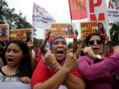 Protesters make cross signs as they shout slogans during a rally outside the U.S. Embassy in Manila, Philippines, Monday, Nov. 24, 2014 to demand justice for the Oct. 11 killing of Filipino transgender Jennifer Laude at the former US naval base of Subic northwest of Manila. U.S. Marine Pfc. Joseph Scott Pemberton was tagged as the suspect in the killing which the protesters termed as a
