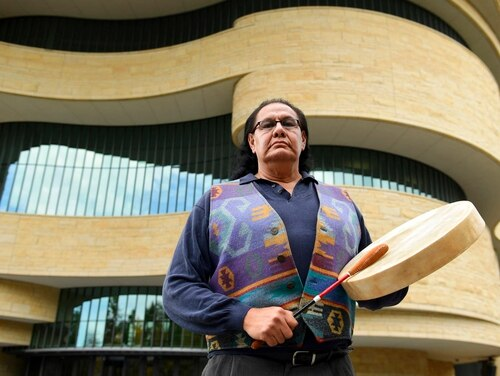 Dennis Zotigh poses for a photo outside the National Museum of the American Indian in Washington, D.C., in November. Many tribes have their own national anthems known as flag songs that focus on veterans, said Zotigh of the Smithsonian National Museum of the American Indian. (Susan Walsh)/Associated Press)