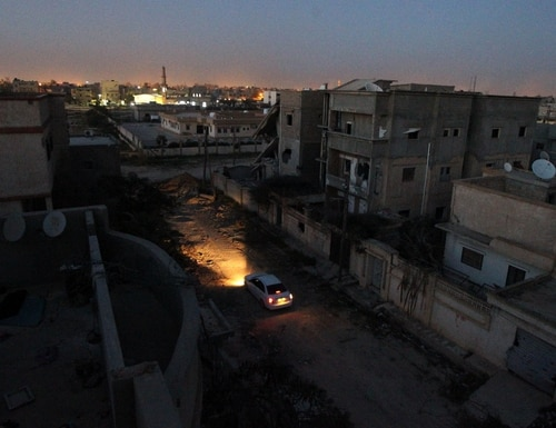 A picture taken on February 27, 2016 shows a car driving at night past damaged buildings after forces loyal to Libya's internationally recognised parliament retook the centre of the eastern coastal city of Benghazi following fierce fighting with armed groups including Islamic State (IS) jihadists. / AFP / ABDULLAH DOMA (Photo credit should read ABDULLAH DOMA/AFP/Getty Images)
