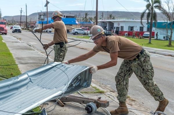 Sailors assigned to the U.S. Navy's Naval Mobile Construction Battalion 1 removes debris from a road during recovery operations following Typhoon Yutu. (Chief Mass Communication Specialist Matthew R. White /Navy)