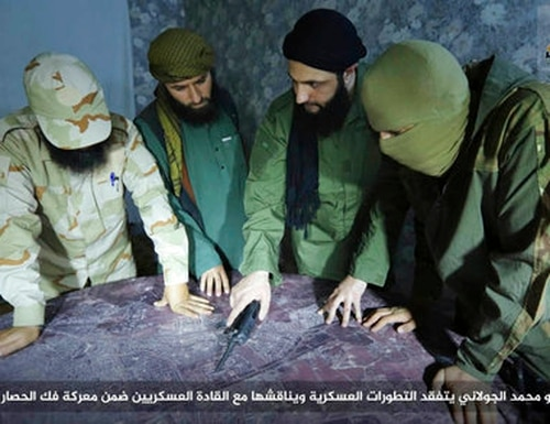 This undated file photo, shows Abu Mohammed al-Golani, second right, then leader of Fatah al-Sham Front, in pictures posted by the group, discussing battlefield details with field commanders over a map, in Aleppo, Syria. (Militant UGC via AP)