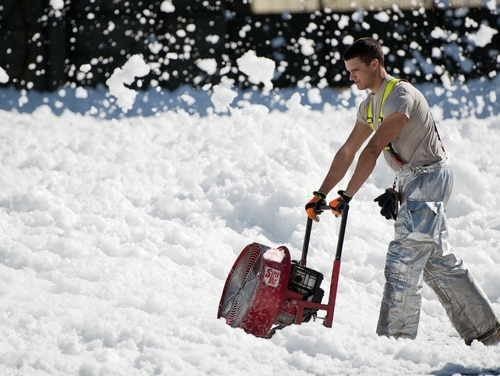 An airman blows a small sea of fire retardant foam that was unintentionally released in an aircraft hangar at Travis Air Force Base, Calif., in 2013. Bills in front of Congress would ban the use of the foam, which has known links to cancer and other conditions. (Ken Wright/Air Force)
