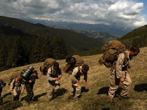United States Marines with Black Sea Rotational Force, Romanian soldiers with the Romanian Mountain Brigade and the British Royal Marine Commandos take a short break after climbing through the Carpathian Mountain Range on a two-day hike during Platinum Lynx, May 7, 2015. The hike consisted of a 40 kilometer alpine movement through snow with an elevation gain of 300 meters of elevation approximately every hour. (USMC photo by Cpl. Ashton C. Buckingham)