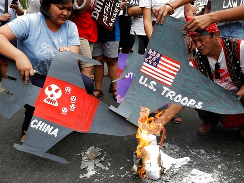Protesters burn cardboard-cut jet fighters with mock U.S. and China flags as they hold a protest in front of the U.S. embassy in Manila, Philippines on Tuesday. (Aaron Favila/AP)