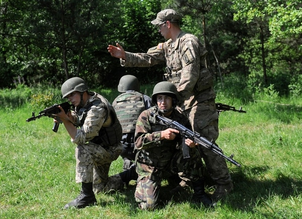 A US soldier, right, instructs Ukrainian soldiers during joint training exercises on the military base in the Lviv region, western Ukraine, Wednesday, June 3, 2015. Troops from the United States and Ukraine conduct joint training exercises intended to help bolster Ukraine's defense against incursions from Russian-backed separatists. (AP Photo/Andrew Kravchenko, Pool)