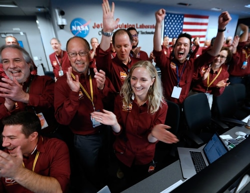 NASA engineers on the flight team celebrate the InSight spacecraft's successfull landing on the planet Mars from the Mission Support area in the Space Flight Operations facility at the NASA Jet Propulsion Laboratory (JPL) in Pasadena, California, on Nov. 26, 2018. (Al Seib/AFP/Getty Images)