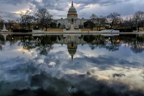 Clouds are reflected in the U.S. Capitol reflecting pool at daybreak in Washington Jan. 22 as day three of the government shutdown continues. (J. David Ake/AP)