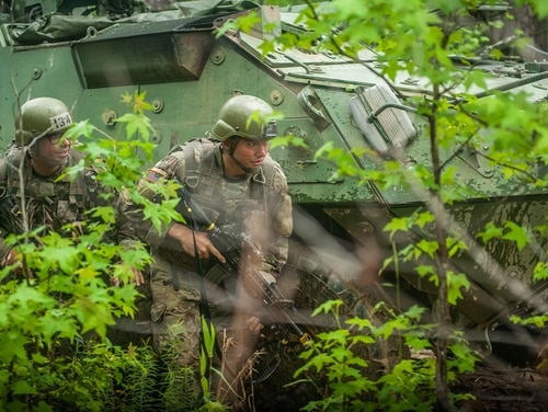 An infantry soldier-in-training assigned to Alpha Company, 1st Battalion, 19th Infantry Regiment, 198th Infantry Brigade, prepares to engage the opposing force. ( Patrick A. Albright/Army)