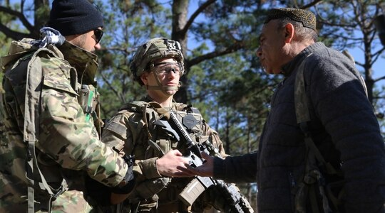 Afghan National Defense Security Forces role players talk to Capt. Justin Alexander, a combat team advisor team leader assigned to the 1st Security Force Assistance Brigade during a simulated event at the Joint Readiness Training Center at Fort Polk, La., Jan. 13, 2018. (Pfc. Zoe Garbarino/Army)