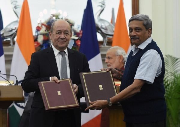 French Defence Minister Jean-Yves Le Drian (L) and his Indian counterpart Manohar Parrikar show off the intergovernmental agreements for the purchase of 36 Rafale jet fighters at a joint press conference in New Delhi on January 25, 2016. India and France have signed an agreement on the long-delayed purchase of 36 Rafale jet fighters but have yet to reach a deal on financial issues, Prime Minister Narendra Modi said on January 25, 2016. AFP PHOTO / Prakash SINGH / AFP / PRAKASH SINGH (Photo credit should read PRAKASH SINGH/AFP/Getty Images)
