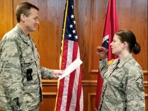 Master Sgt. Robin Brown, right, a public affairs officer with the Tennessee Air National Guard, recites her oath of re-enlistment using a dinosaur hand puppet in an April 13 video. (Screenshot of video from Facebook)