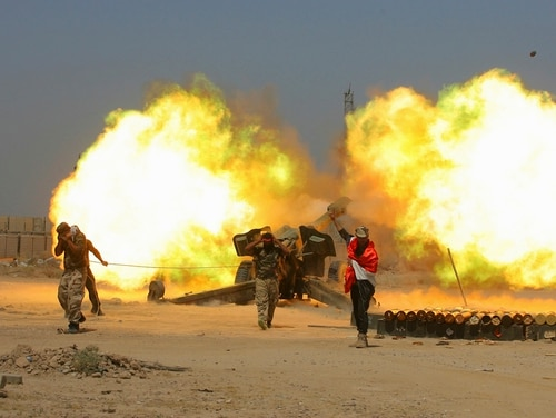 In this May 29, 2016, file photo, Iraqi security forces and allied Popular Mobilization forces fire artillery during fight against Islamic State militants in Fallujah, Iraq. (Anmar Khalil/AP)