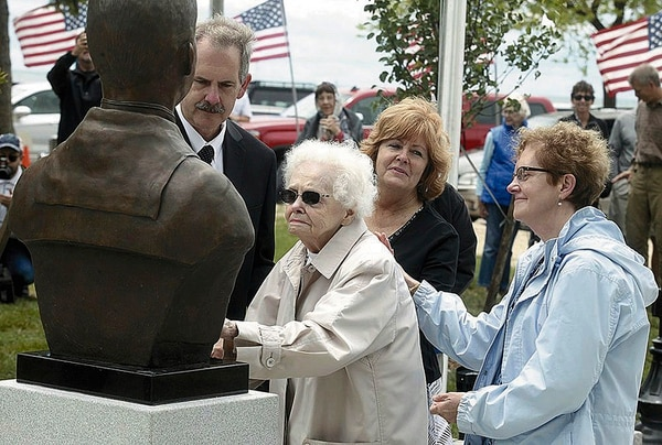 In this 2017 photo, Peg Ezdebski, surrounded by her children, looks at a bronze bust of her brother, and Medal of Honor recipient William Charette, that was placed in the Veterans Memorial in Stearns Park in Ludington, Mich. (Jeff Kiessel/Ludington Daily News via AP)