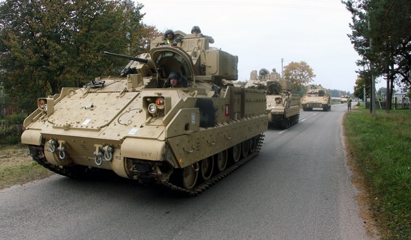Members of the US Army 1st Brigade, 1st Cavalry Division, drive Bradley Fighting Vehicles from the railway station near the Rukla military base in Lithuania, on October 4, 2014. Lithuania will increase its defence budget by a third next year amid concerns over a resurgent Russia, but spending will still fall short of NATO's recommended two percent of output, officials said on October 2, 2014. AFP PHOTO / PETRAS MALUKAS (Photo credit should read PETRAS MALUKAS/AFP/Getty Images)