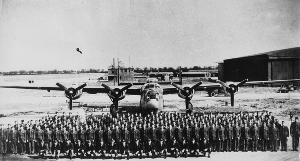 Personnel of the 489th Bombardment Group with a B-24 Liberator and the control tower at Halesworth, England. The plane pictured here is the same model that Sgt. Duran crashed landed into the Slovenian countryside in 1944. (Courtesy Photo)