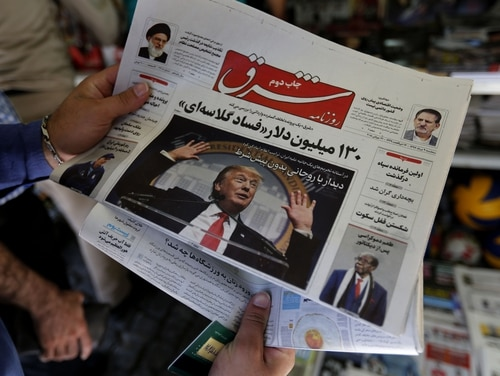 A man takes a glance at a newspaper with a picture of US president Donald Trump on the front page, in the capital Tehran on July 31, 2018. In Washington, the U.S. House is expected to vote this week on several measures to limit the president's power to wage war on Iran and aid the Saudi campaign in Yemen after they cleared a key procedural hurdle Tuesday night. (ATTA KENARE/AFP/Getty Images)
