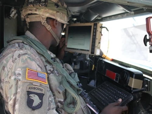 A soldier boots up his system inside what is essentially a Warfighter Information Network-Tactical system on a Humvee. (Jen Judson/Staff)
