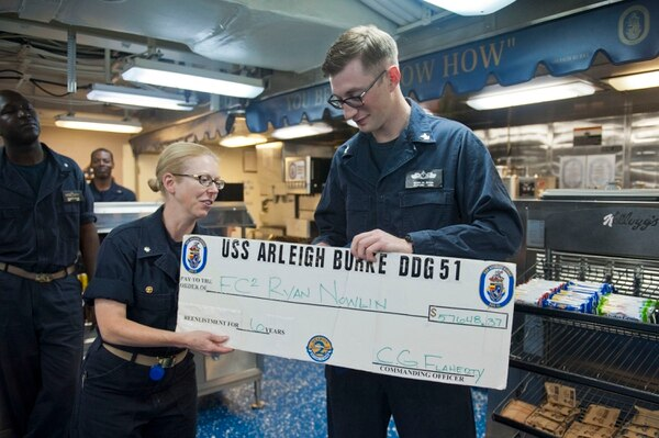 140508-N-WD757-396 ARABIAN GULF (May 8, 2014) Cmdr. Camille Flaherty, commanding officer of the guided-missile destroyer USS Arleigh Burke (DDG 51), presents Fire Controlman 2nd Class Ryan Nowlin, from Wakeeney, Kan., a re-enlistment bonus check during his re-enlistment ceremony. Arleigh Burke is deployed in the U.S. 5th Fleet area of responsibility supporting maritime security operations and theater security cooperation efforts. (U.S. Navy photo by Mass Communication Specialist 2nd Class Carlos M. Vazquez II/Released)
