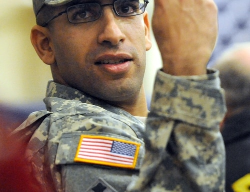 In this photo taken on Feb. 14, 2013, Capt. Florent Groberg watches the Change of Command ceremony for the 4th Infantry Brigade Combat Team at the Fort Carson Special Events Center, in Colo. Groberg will receive the Medal of Honor next month in a ceremony at the White House. (Christian Murdock/The Gazette via AP) MAGS OUT; MANDATORY CREDIT