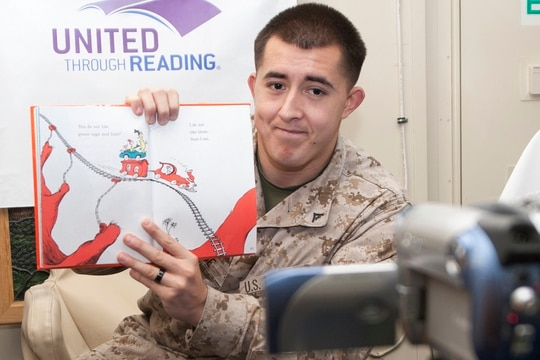 Lance Cpl. Matthew Payne, from San Diego, reads a book for his loved ones during a United Through Reading session aboard the amphibious assault ship Boxer (LHD 4) in 2013. (Mass Communication Specialist 1st Class Jennifer Gold/Navy)