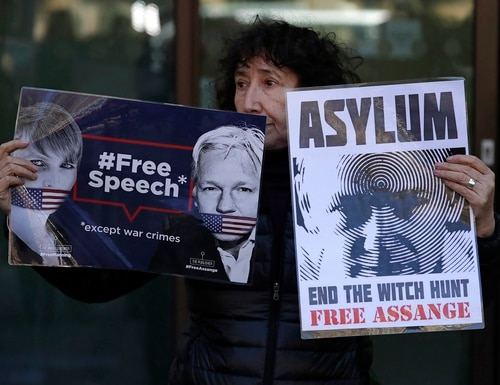 A protester demonstrating in support of WikiLeaks founder Julian Assange holds placards outside Westminster magistrates court where he was appearing in London, Thursday, April 11, 2019. Police in London arrested WikiLeaks founder Assange at the Ecuadorean embassy Thursday, April 11, 2019, for failing to surrender to the court in 2012, shortly after the South American nation revoked his asylum. (Matt Dunham/AP)