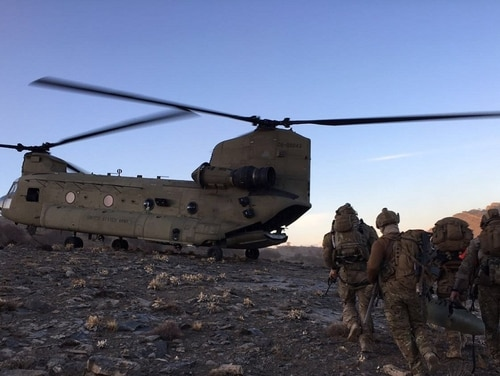 Rescue squadron airmen prepare to board a U.S. Army CH-47 Chinook at an undisclosed location in Afghanistan. During the recent Ghazni city siege, a pararescue jumper was reportedly wounded and received the Purple Heart. (DoD)