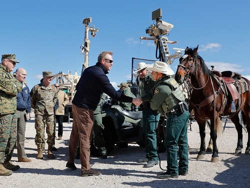 Acting Secretary of Defense Patrick Shanahan, center, greets Border Patrol Agents Carlos Lerma, second from the right, Moises Gonzalez, right, and the horse they use for patrols during a tour of the US-Mexico border at Santa Teresa Station in Sunland Park, N.M., Saturday, Feb. 23, 2019. (Pablo Martinez Monsivais/AP)